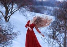 Uma moça dança no vento, seu cabelo está vibrando belamente A pose é clara e pairosa, um sentido da liberdade imagem de stock