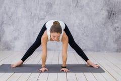 Uma moça desportivo que estica os pés, classe da ioga Mulher loura que senta-se na guita fotos de stock