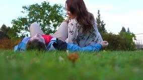 Uma moça e um indivíduo que encontram-se no gramado video estoque