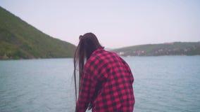 Uma moça em uma camisa de manta vermelha que levanta para a câmera A menina está sentando-se na costa do lago em um dia morno video estoque