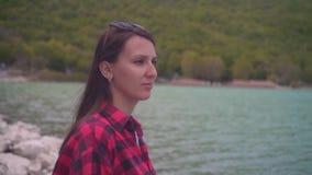 Uma moça em uma camisa de manta vermelha que levanta para a câmera A menina está sentando-se na costa do lago em um dia morno vídeos de arquivo