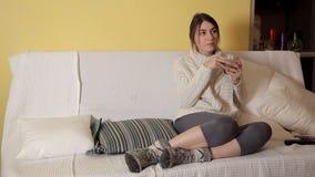 Uma moça em uma camiseta morna acolhedor em um inverno que nivela em casa o chá bebendo e que pensa sobre algo video estoque