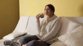 Uma moça em uma camiseta morna acolhedor em um inverno que nivela em casa o chá bebendo e que pensa sobre algo filme