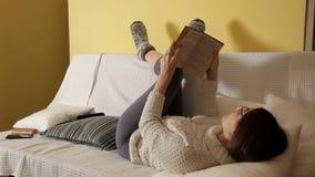 Uma moça em uma camiseta morna acolhedor em um inverno que nivelam em casa, em vidros, lendo um livro e uma queda adormecidos Cas video estoque