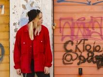 Uma moça em um chapéu feito malha e em um revestimento vermelho está contra a parede pintada de uma garagem fotografia de stock