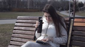 Uma moça em um fato de esporte no parque no banco que lê um livro e que bebe o café de uma caneca térmica Gire vídeos de arquivo