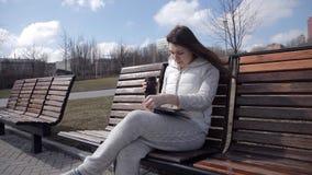 Uma moça em um fato de esporte no parque no banco que lê um livro e que bebe o café de uma caneca térmica Gire video estoque