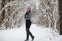 Uma moça em um parque do inverno em uma caminhada Feriados do Natal em t fotografia de stock royalty free