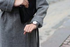 uma moça em um revestimento cinzento olha seu relógio de pulso, verifica o tempo, olha seu relógio a pressa a uma reunião, esteja fotografia de stock royalty free