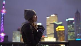 Uma moça em um revestimento preto e em caminhadas do chapéu em torno do Shanghai bonito com café em suas mãos filme