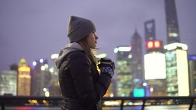 Uma moça em um revestimento preto e em caminhadas do chapéu em torno do Shanghai bonito com café em suas mãos video estoque