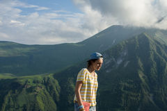 Uma moça em um t-shirt listrado e em um tampão no verão nas montanhas do conto de fadas e em um fundo misterioso do céu foto de stock