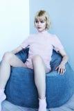 Uma moça em um terno home cor-de-rosa perto de uma cadeira macia Poses modelo bonitas para o compartimento de forma Imagem em ton Foto de Stock Royalty Free
