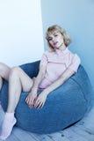 Uma moça em um terno home cor-de-rosa perto de uma cadeira macia Poses modelo bonitas para o compartimento de forma Imagem em ton Fotos de Stock