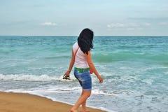 Uma moça em um Tshirt branco está andando ao longo da areia no mar morena na costa do mar dos azuis celestes em Bulgária fotografia de stock royalty free
