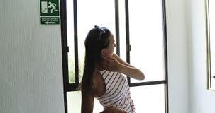 Uma moça em um vestido com uma mala de viagem nas rodas olha no espelho na entrada do hotel video estoque