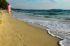 Uma moça em um vestido cor-de-rosa anda com os pés descalços ao longo da praia de Camboja fotos de stock