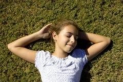 Uma moça encontra-se na grama segada que estica seus braços Imagens de Stock