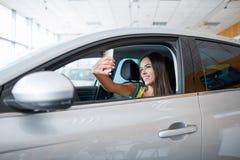 Uma moça escolhe um carro novo para si mesma Comprando um carro novo Fotografia de Stock
