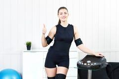 Uma moça está ao lado do treinamento do EMS do simulador foto de stock