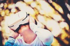 Uma moça está apreciando seu mundo pessoal com uns auriculares de VR imagens de stock