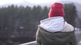 Uma moça está em um revestimento e em um chapéu na ponte e toma uma foto, durante uma queda de neve movimento lento, 1920x1080, c filme