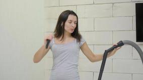 Uma moça está limpando a casa usando um aspirador de p30 e dançada vídeos de arquivo