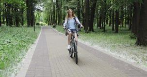 Uma moça está montando bicicletas em parques do verão filme