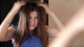 Uma moça está na frente de um espelho, penteando seus cabelo e virada por seu cabelo vídeos de arquivo