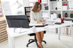 Uma moça está sentando-se na mesa do computador no escritório, guardando um lápis em sua mão e fazendo anotações no imagens de stock