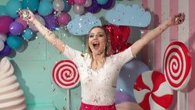 Uma moça feliz joga acima um ouropel colorido em um partido Movimento lento filme