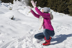 Uma moça joga com neve no inverno Fotos de Stock Royalty Free