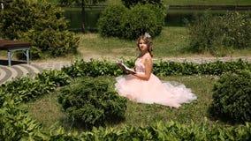 Uma moça lê um livro na grama no parque video estoque
