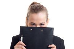 Uma moça mantém uma cara preta da tabuleta isolada no fundo branco Foto de Stock