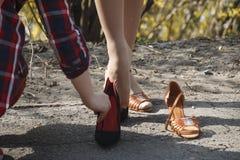 Uma moça na rua decola seus calçados casuais e põe sobre a roupa do feriado imagem de stock royalty free