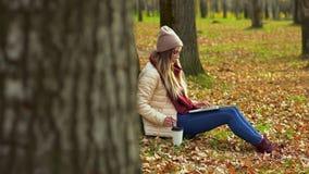 Uma moça no parque do outono perto da árvore, sentando-se com um portátil, café bebendo filme
