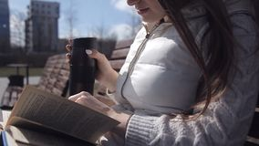 Uma moça no parque em um banco que lê um livro e que bebe o café de uma caneca Fim acima video estoque