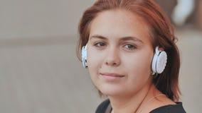 Uma moça nos fones de ouvido brancos com prazer escuta a música filme