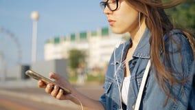 Uma moça nos vidros senta-se na rua e escuta-se a música em fones de ouvido Cabelo de vibração no close-up do vento video estoque