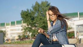 Uma moça nos vidros senta-se na rua e escuta-se a música em fones de ouvido A menina com o telefone à disposição e dentro video estoque