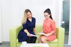 Uma moça obtém o conselho de um cosmetologist, um especialista da dieta, sentando-se em um sofá verde fotos de stock