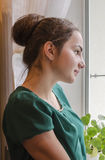 Uma moça olha para fora a janela Foto de Stock