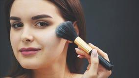 Uma moça põe um pó para sua cara com uma escova da composição Aplicação da composição no close-up isolado em um preto video estoque