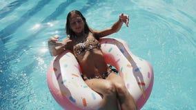 Uma moça passa o tempo na associação, toma sol em um círculo inflável e em nadadas na água vídeos de arquivo