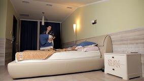 Uma moça prepara-se para a cama, remove-se a colcha da cama e remove-se a vídeos de arquivo