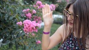 Uma moça que anda em um parque do verão dobrado para baixo para sentir o cheiro de flores cor-de-rosa bonitas, o cheiro era desag video estoque