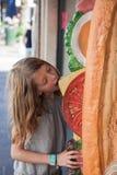 Uma moça que come o sanduíche falsificado gigante Foto de Stock