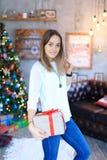Uma moça que está com presente amarrou a fita vermelha no smili das mãos Foto de Stock Royalty Free