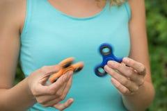 Uma moça que guarda e que torce dois giradores do azul e do orangotango Fotografia de Stock Royalty Free