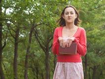 Uma moça que guarda um livro Imagem de Stock